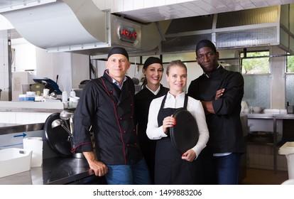 Portrait of confident smiling team of chefs in interior of restaurant kitchen