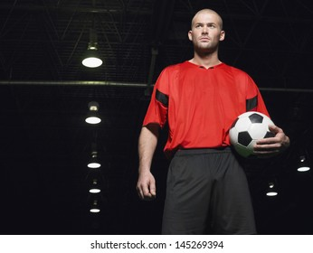 Portrait of a confident soccer player holding ball
