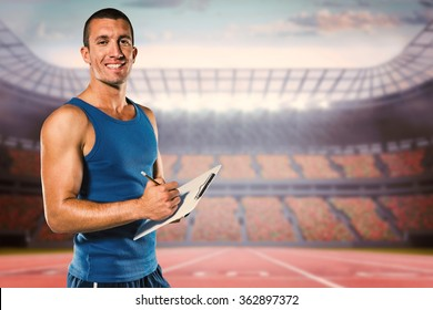 Portrait of confident sports coach writing on clipboard against race track