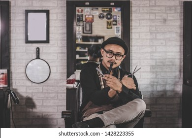 portrait of confident stylist man barber sitting at vintage barbershop chair holding two's scissor facing and looking at camera