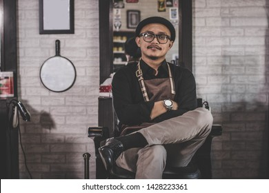portrait of confident stylist man barber sitting at vintage barbershop chair with crossed arm facing and looking at camera