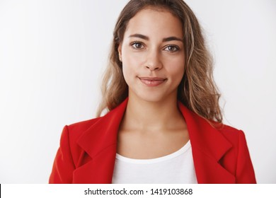 Portrait confident successful good-looking happy young curly-haired modern businesswoman wearing red jacket smiling self-assured expressing positive lucky vibe, grinning ambitious reach goal