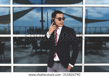 Portrait of a confident successful men entrepreneur dressed in luxury clothes having mobile phone conversation outdoors, young asian businessman talking on cellphone while standing near office window