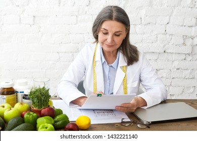 Portrait of confident successful middle aged European woman dietician sitting at her workplace with laptop and vegetables on desk, developing dietary plan for her client with nutritional problems