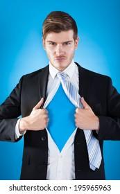 Portrait of confident superhero businessman tearing suit against blue background