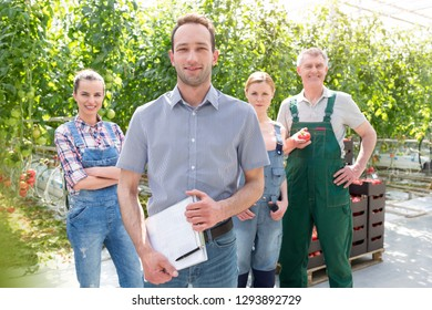 Portrait of confident supervisor and gardeners standing at greenhouse