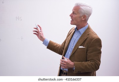 portrait of confident teacher solving problems on whiteboard in classroom