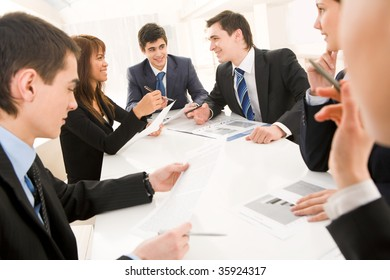 Portrait of confident team discussing documents and interacting with each other at briefing