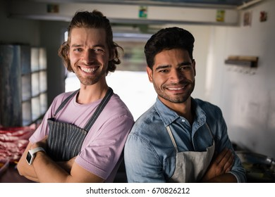 Portrait of confident waiters standing with arms crossed at food truck counter