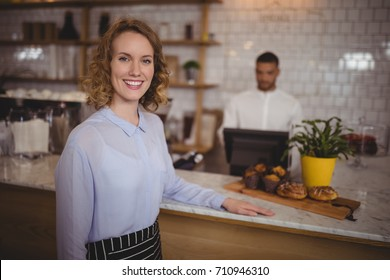 Portrait of confident waitress standing by counter at coffee shop