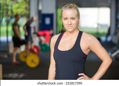 Portrait of confident woman with hand on hip standing in gym