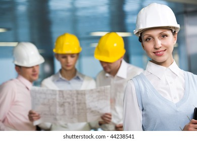 Portrait of confident woman in helmet looking at camera in working environment