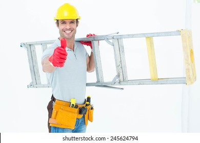 Portrait of confident worker carrying step ladder while showing thumbs up over white background