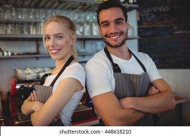 Portrait of confident workers standing with arms crossed at cafe