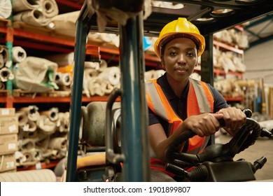 Portrait of a confident young African female forklift operator working in a textile warehouse