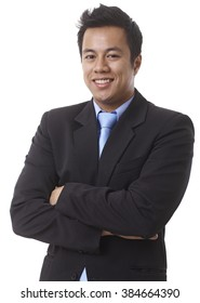 Portrait of confident young Asian businessman smiling arms crossed, looking at camera.