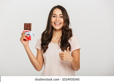 Portrait of a confident young asian woman holding chocolate bar and showing thumbs up isolated over white background