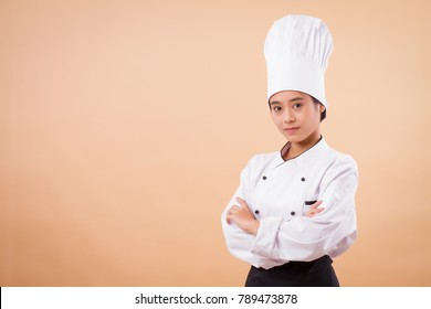 portrait of confident young asian woman chef; confident woman chef; young professional female cooking staff, girl pastry chef, woman cook or female baker; successful asian chef studio isolated