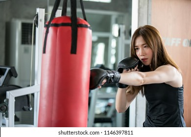 Portrait of a confident young athlete woman posing in boxing gloves, punching A Bag in professioal gym.