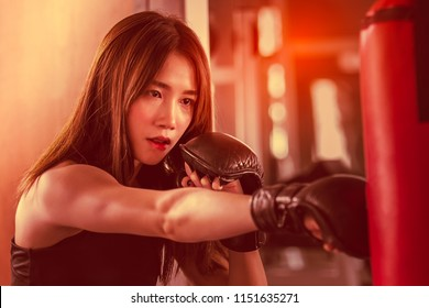 Portrait of a confident young athlete woman posing in boxing gloves, punching bag in professioal gym. Asian boxing girl.