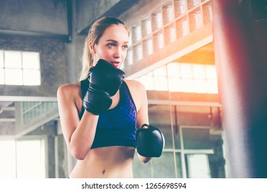 Portrait of a confident young athlete woman posing in boxing gloves, punching A Bag in professioal gym. Strong caucasian girl practising boxing with huge red sand bag.