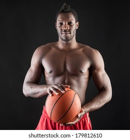 Portrait of confident young black man shirtless with basket ball against black background.