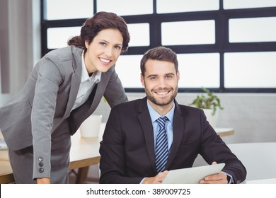 Portrait of confident young business people at desk in office