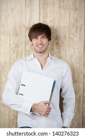 Portrait of confident young businessman with binder standing against wooden wall
