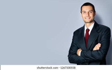 Portrait of confident young businessman in black suit and red tie, with crossed arms pose, empty copy space place for some text, advertising or slogan, standing over grey background