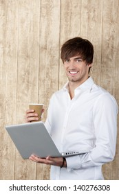 Portrait of confident young businessman with cup and laptop standing against wooden wall