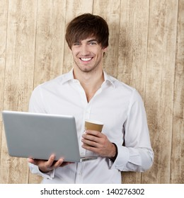 Portrait of confident young businessman with disposable cup and laptop standing against wooden wall