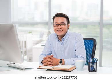 Portrait of confident young businessman at his workplace