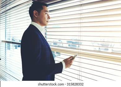 Portrait of a confident young businessman holding cell telephone while standing near office window, intelligent men in elegant suit waiting for a call on his mobile phone while resting after meeting