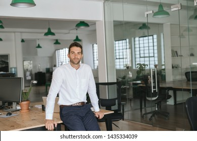 Portrait of a confident young businessman leaning against a table while working alone in a large modern office