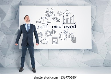 Portrait of confident young businessman standing with clenched fists near wall with self employed sketch and looking upwards. Concept of being your own boss.
