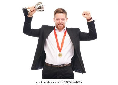 Portrait of confident young businessman wearing medal and holding trophy on white background
