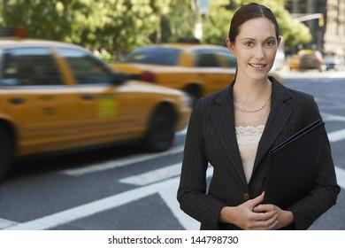 Portrait of a confident young businesswoman holding portfolio on street