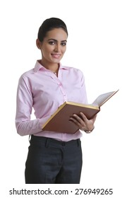 Portrait of confident young businesswoman holding diary over white background