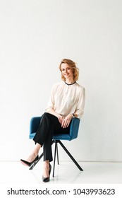 Portrait of a confident young businesswoman sitting in a chair against white background
