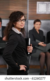 Portrait of confident young businesswoman standing in office with hand on her hip, looking back.?