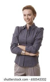 Portrait of confident young businesswoman standing arms crossed, smiling, looking at camera.