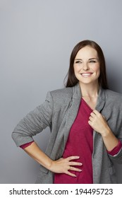 portrait of a confident young businesswoman. Wearing gray jacket over purple top. On gray studio background with space for text