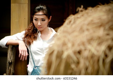 Portrait of a confident young cowgirl standing beside thatch looking for something