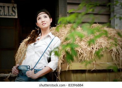 Portrait of a confident young cowgirl standing beside thatch loo