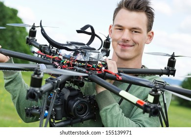 Portrait of confident young engineer holding UAV with camera in park