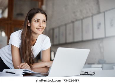 Portrait of confident young female entrepreneur standing near laptop computer looking forward into her future millionaire house.