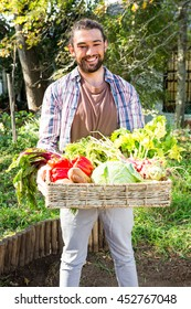 Portrait of confident young hipster gardener with vegetables in basket at garden