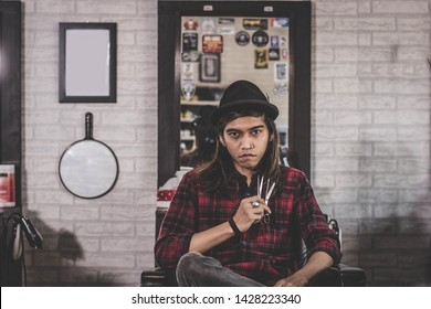 portrait of confident young long hair stylist barber sitting at vintage barbershop chair holding two's scissor facing and looking at camera