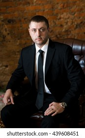 A portrait of a confident young man in a black suit. Businessman looks at us