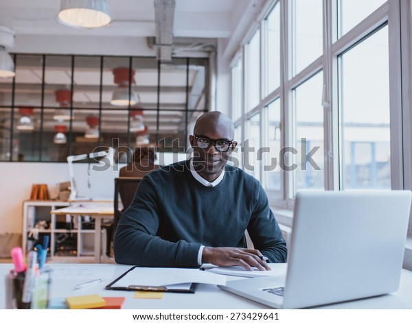 Portrait of confident young man sitting at his desk with laptop. African businessman working in modern office.